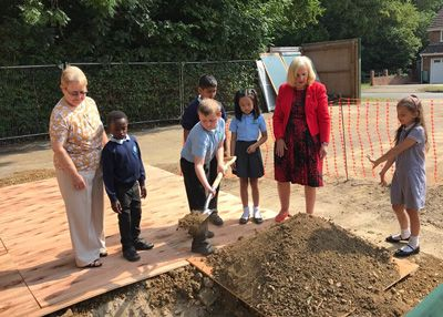 Children burying a time capsule at Addison House