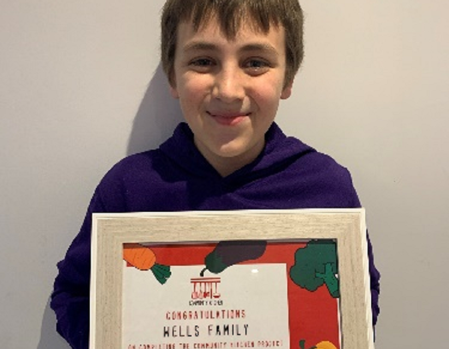 Tommy holding up his certificate after attending the Community Kitchen Programme
