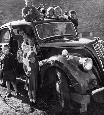 Children form Lodge Farm Infants School in 1964 with their new car!