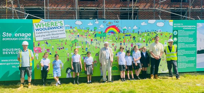 Children and adults standing in front of new hoarding